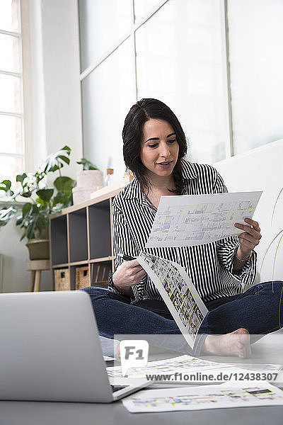 Casual woman with sheets of paper and laptop sitting on the floor in office