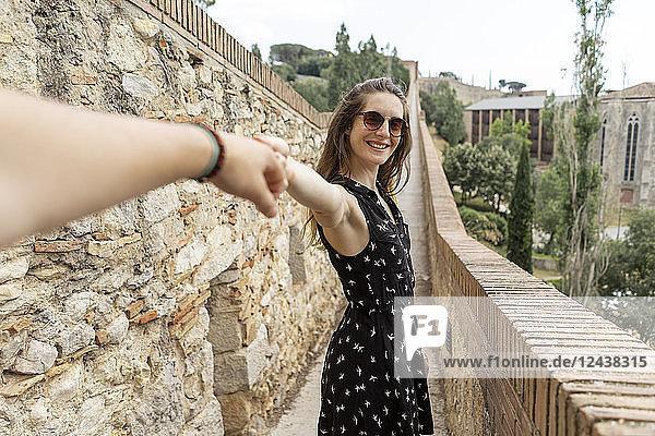 Spain  Girona  smiling woman holding man's hand walking along stone wall