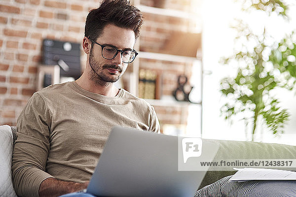 Portrait of man sitting on couch at home using laptop