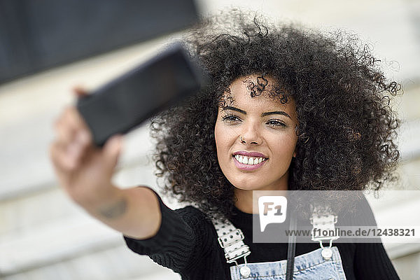 Portrait of smiling young woman taking selfie with smartphone