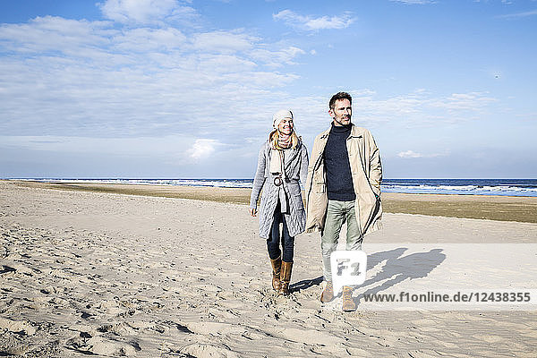Couple in warm clothing walking on the beach