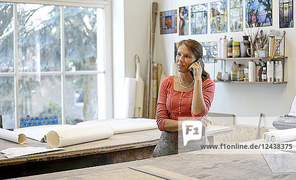 Woman talking on cell phone in glazier's workshop