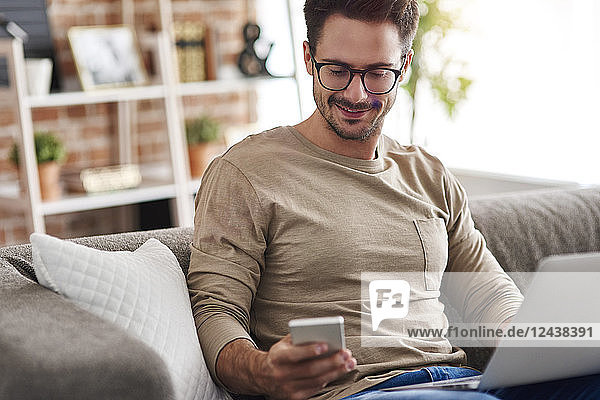 Smiling man sitting on couch at home using laptop and cell phone