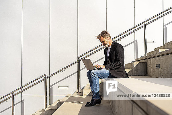 Businessman sitting on steps outdoors using laptop
