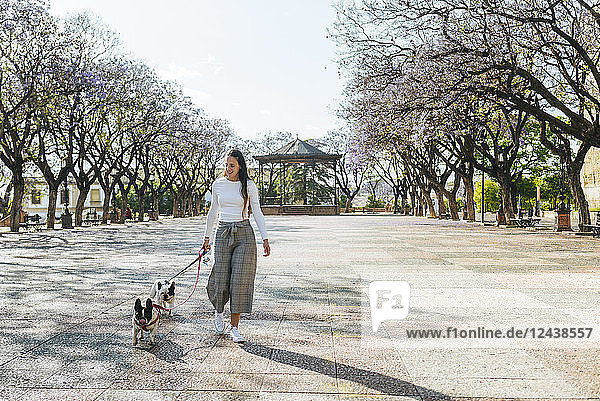 Spain  Andalusia  Jerez de la Frontera  Woman walking with two dogs on square