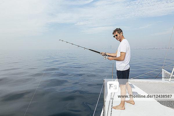 Mature man standing on catamaran  fishing