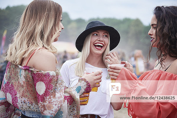 Friends drinking juice and sitting on meadow during music festival
