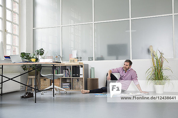 Casual man with plans sitting on the floor in a loft office