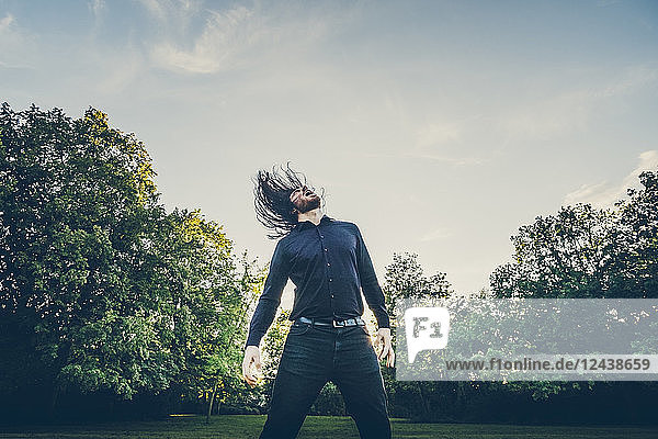 Heavy metal fan headbanging in a park