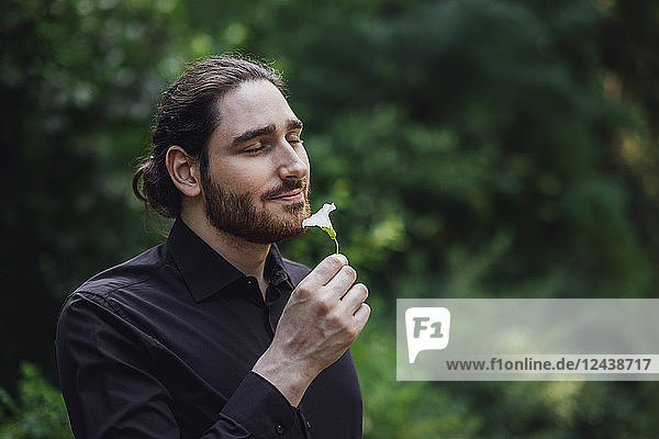 Young man  dressed in black  standing in park  smelling flower