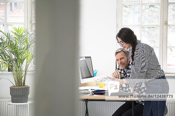 Colleagues discussing document at desk in office