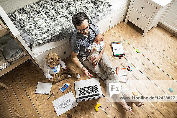 Father with his little son and baby daughter working from home