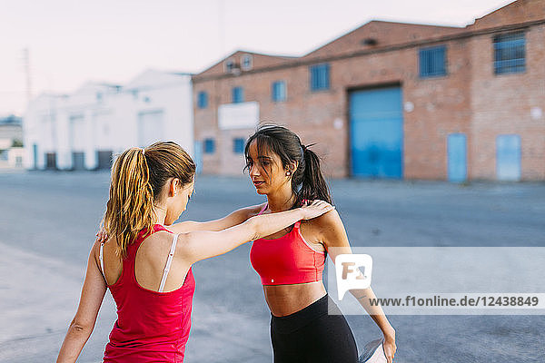 Two active women stretching and supporting each other