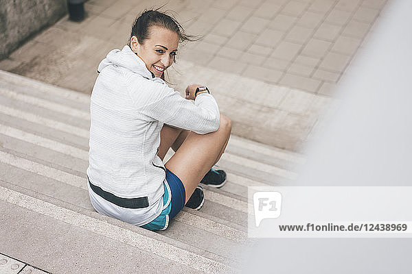 Smiling sportive young woman sitting on stairs outdoors