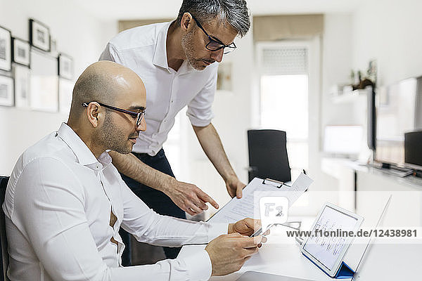 Two colleagues working at home with tablet and documents