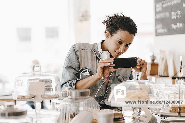 Woman taking pictures of cakes in coffee shop with her smartphone