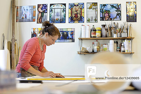 Woman working on draft in glazier's workshop Woman working on draft in glazier's workshop