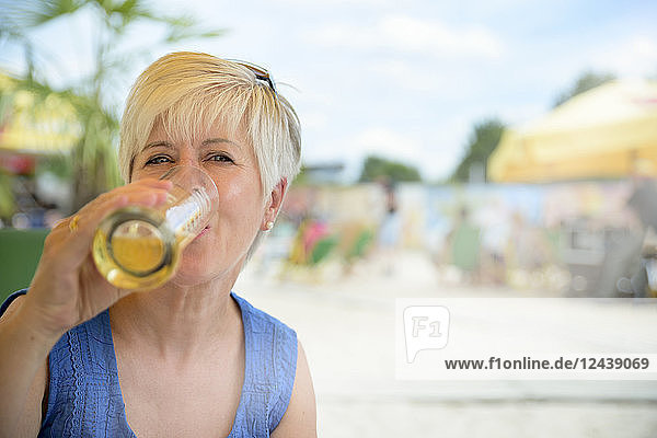 Portrait of senior woman drinking beer at beach bar