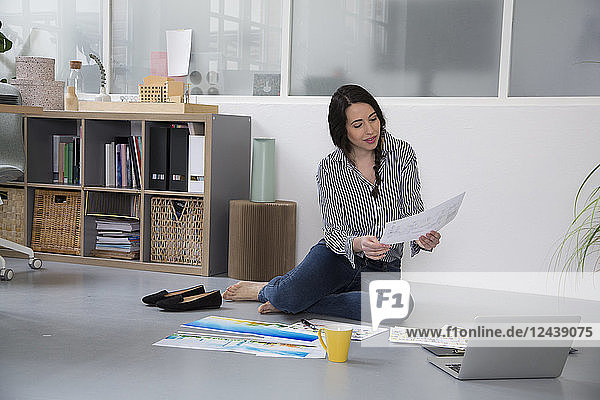 Casual woman with plans and laptop sitting on the floor in a loft office