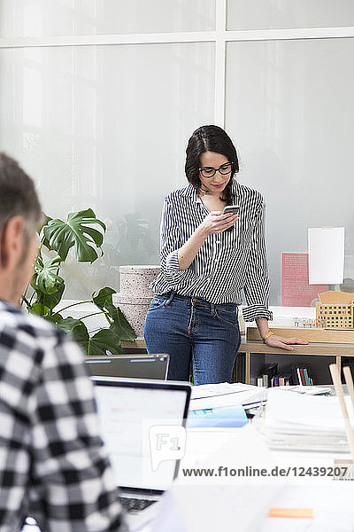 Portrait of woman with colleague using cell phone in office