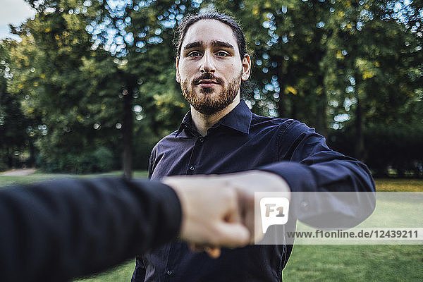 Young businessman greeting business partner in a park  negotiating business transactions