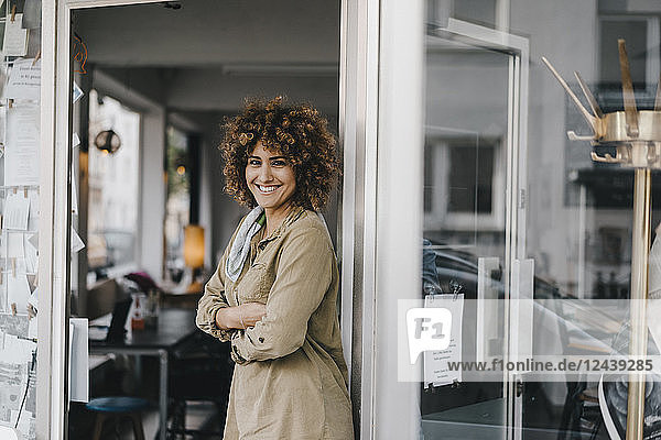 Smiling woman standing with arms crossed in door of coworking space