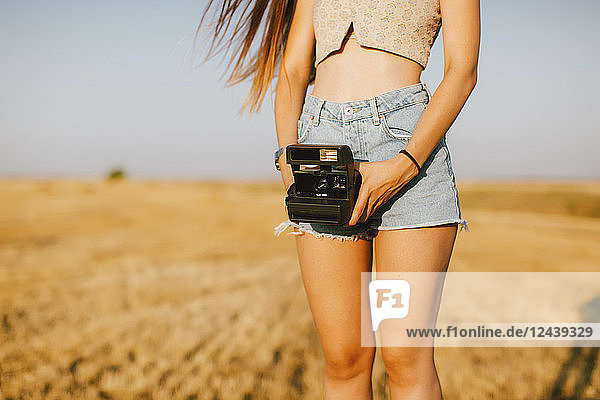 Young woman with instant camera on a field at sunset  partial view