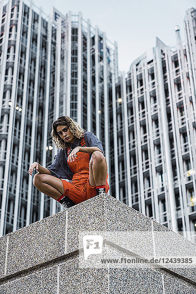 Beautiful woman wearing dungarees  crouching on ledge in front of modern high-rise building