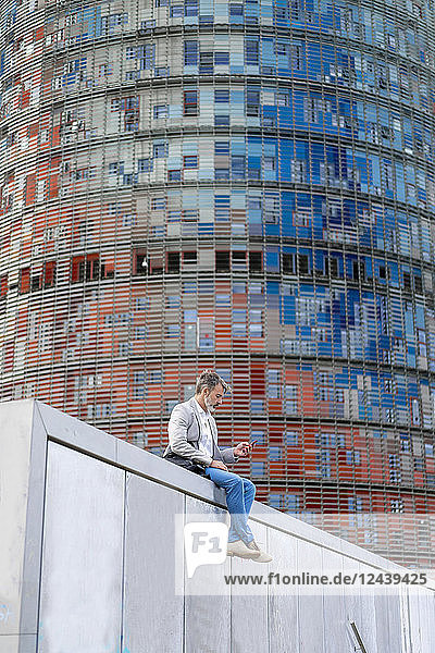 Spain  Barcelona  businessman sitting on wall using cell phone