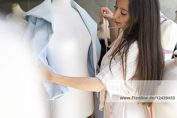 Young fashion designer fitting clothes on dressmaker's model Young fashion designer fitting clothes on dressmaker's model