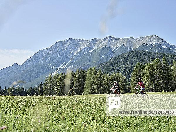 Austria  Tyrol  Mieming  couple riding bike in alpine scenery