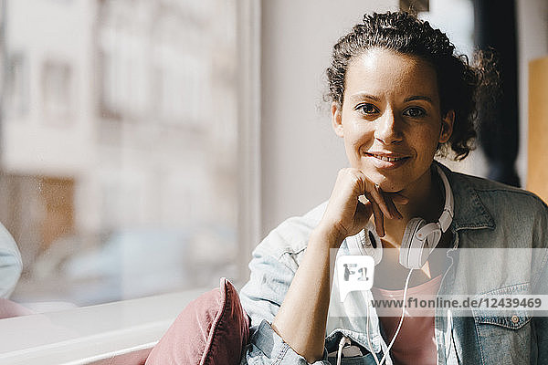 Young woman with headphones  working in coworking space