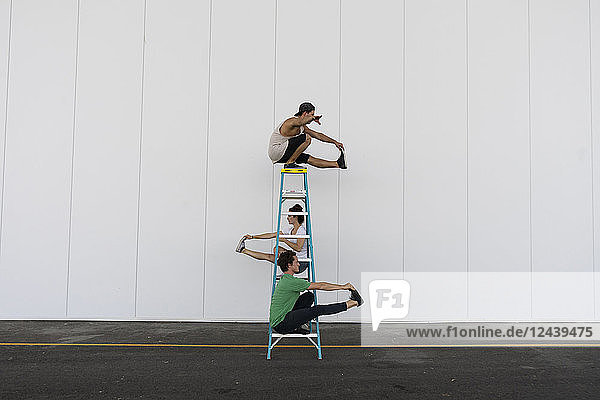 Three acrobats doing tricks on a ladder