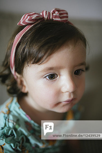 Portrait of concentrated baby girl at home