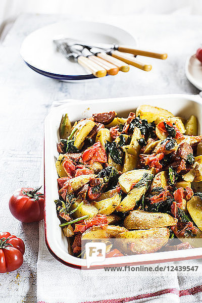 Casserole with potatoes  spinach  tomatoes and chorizzo