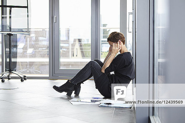 Overstressed businesswoman sitting on the floor in office