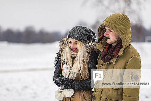 Happy young couple in park on a snowy day