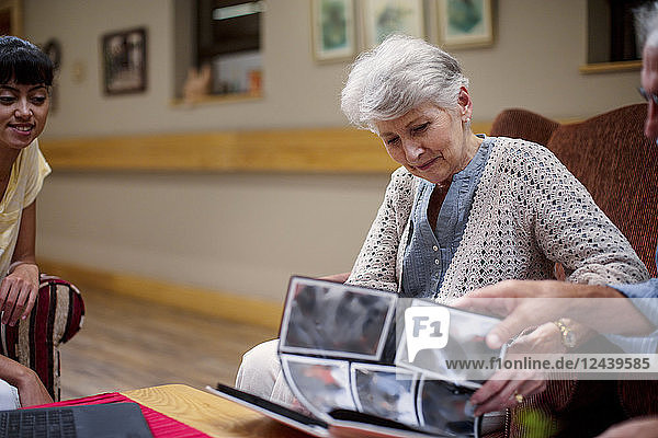 Seniors at retirement home looking at photo albums