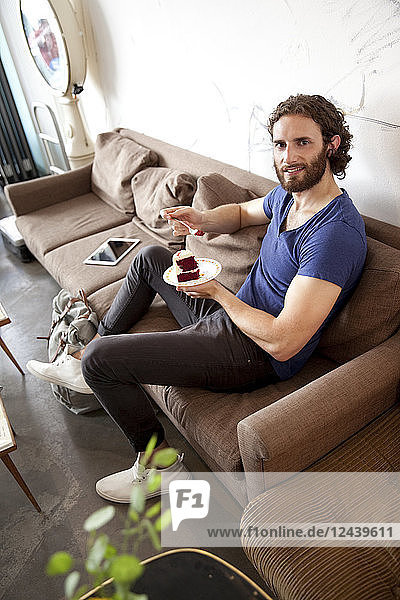 Portrait of relaxed young man sitting on couch in a coffee shop eating fancy cake