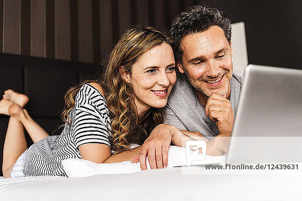 Happy couple lying on bed at home looking at laptop
