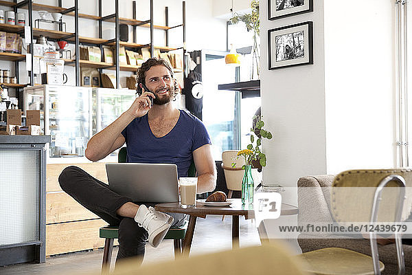 Portrait of young man on the phone sitting in a coffee shop with laptop