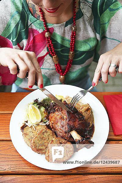 Close-up of woman eating Schweinshaxe in street restaurant
