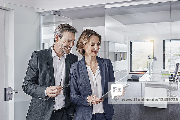 Smiling businessman and businesswoman using tablet in office together