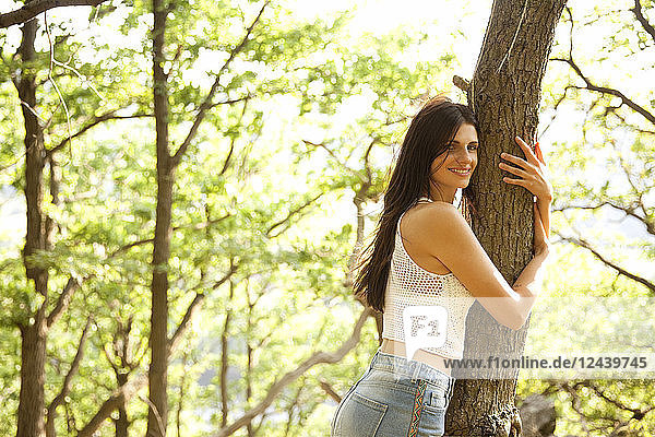 Young woman in forest hugging a tree