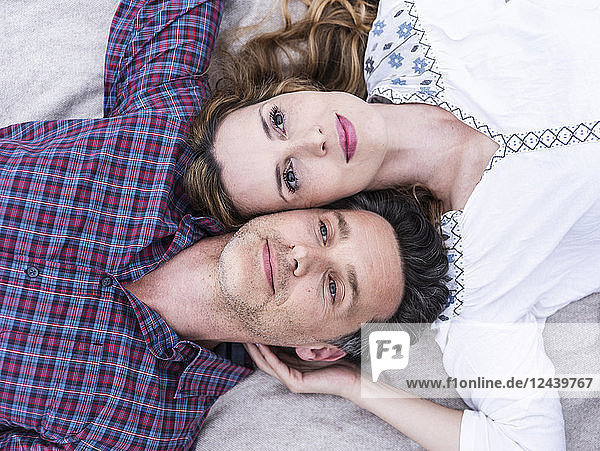 Portrait of affectionate couple lying on a blanket