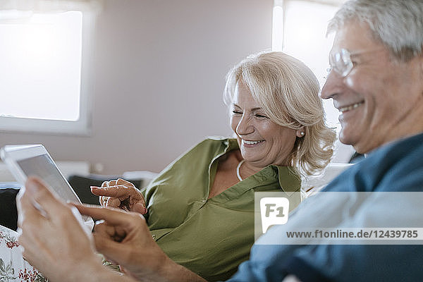 Happy senior couple at home sitting on couch using tablet