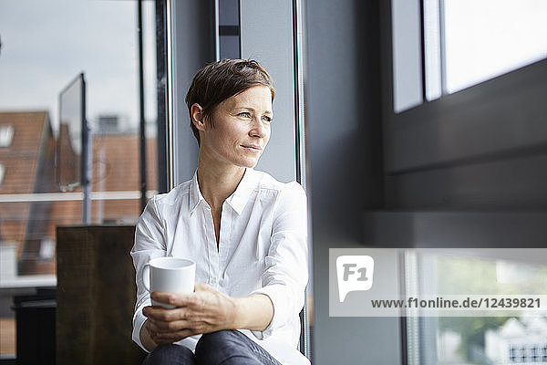 Businesswoman sitting in office with cup of coffee looking out of window