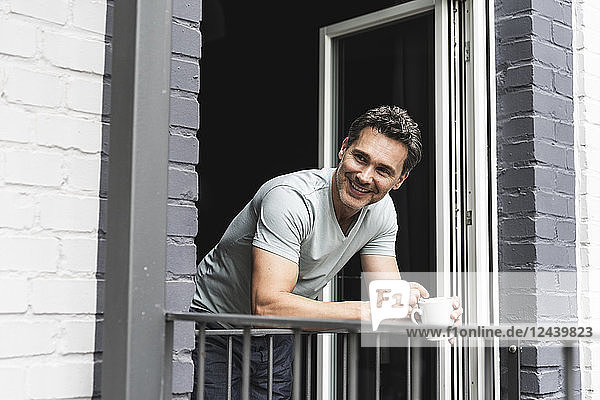 Smiling man in pyjama at home with cup of coffee looking out of balcony door