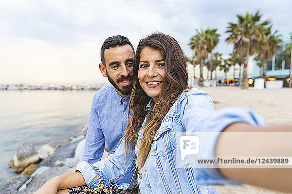 Spain  Barcelona  smiling couple taking a selfie at the seaside