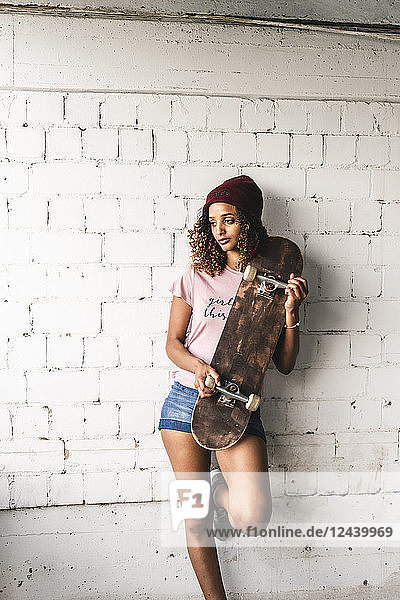 Portrait of a young woman with skateboard  leaning against wall